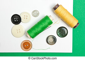 thread with a needle and buttons on the background of the...