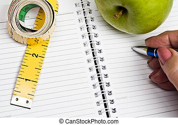Measurement tape and apple - Measurement tape and apple on...