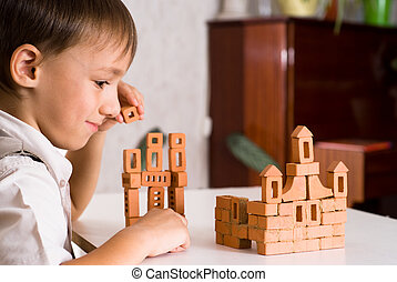 handsome boy builds a toy castle on a white background