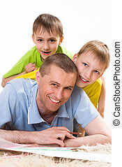 father and two young brothers lying on the carpet