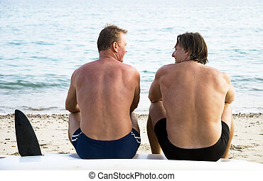 two mature men chatting on beach together while sitting on...