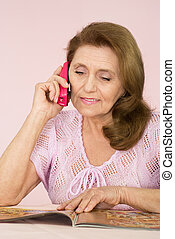 Pretty old woman with a phone on a pink background