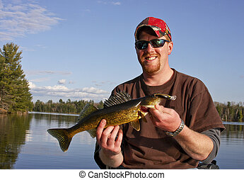 walleye fishing - fisherman holding a walleye sitting in a...