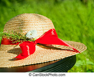 straw hat with red ribbon in the grass