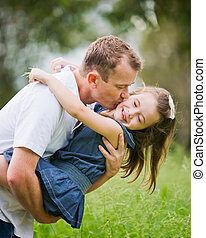 A 6 year old girl enjoying a moment of fun with her dad who...