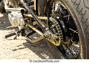 motorcycle wheel and drive-chain with golden toned...