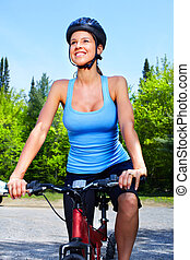 Woman cyclist. - Young woman cyclist riding  in the park