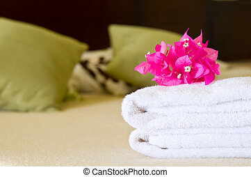 Hotel room service - White towels with flowers on a bed in a...
