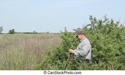hunter loading shotgun and shooting