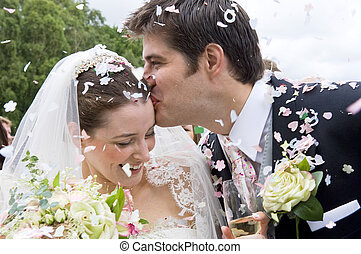 Bride and Groom in confetti shower - A really happy looking...