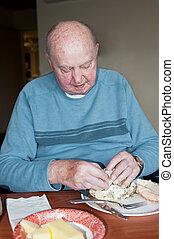 Elderly Man Eating Dinner - An elderly man eating dinner in...