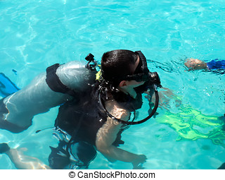 Learning to scuba dive - A boy learning to scuba dive during...