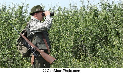 hunter with binoculars and rifle