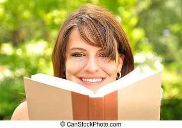 Reading outdoors - A young woman reading a book outdoors