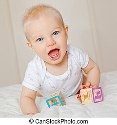 A 7 month old baby boy looking up from playing with blocks