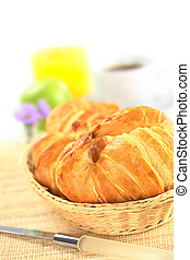 Fresh croissants in bread basket with coffee, orange juice and a green apple in the back (Selective Focus, Focus on the front of the croissant)