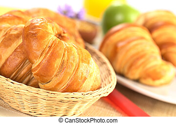 Fresh croissants in bread basket with a red knife beside, and a plate with croissants, green apple and orange juice in the back (Selective Focus, Focus on the front of the croissant in the basket)