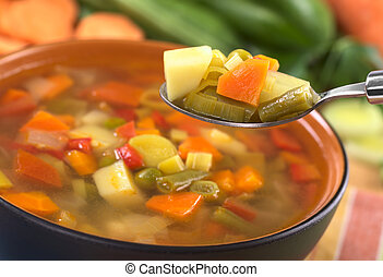 Fresh vegetable soup on spoon made of green bean, pea, carrot, potato, red bell pepper, tomato and leek in black bowl with ingredients in the back (Selective Focus, Focus on the carrot, leek and green