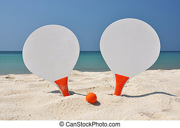 Two racket and a ball on the sandy beach