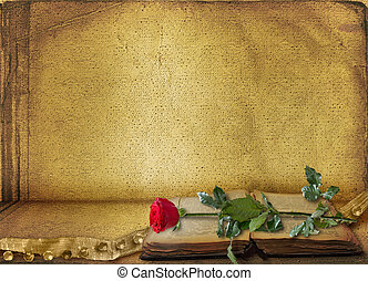 Open ancient book with beautiful red rose