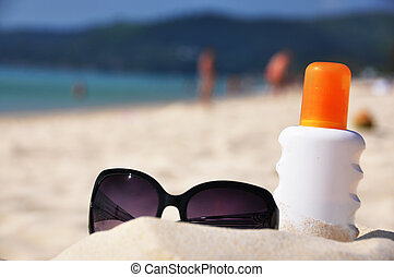 Sunglasses and sun lotion on the beach of Phuket island,...
