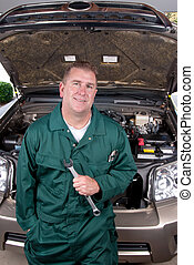 Auto mechanic - An auto mechanic holds a wrench before...