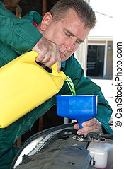 Car radiator maintenance - A mechanic pours radiator fluid...