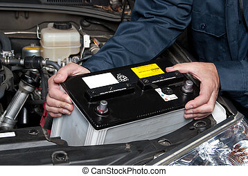 Auto mechanic replacing car battery