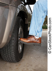 Kicking the tire - A man kicks his car tire to make sure its...
