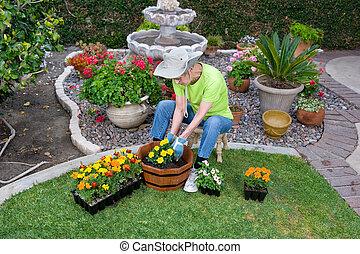Adult Senior planting flowers - A senior adult plants...