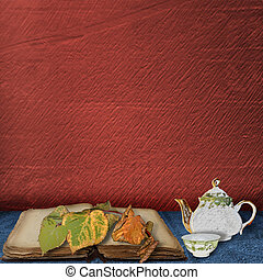 The old book with leaves and teapot with cup of tea on the...