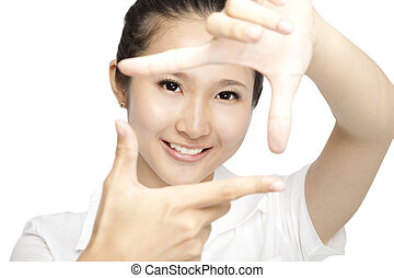 Portrait of smiling young woman making a hand frame isolated...