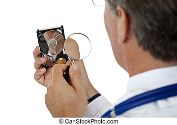 Doctor checks computer harddisk with magnifying...