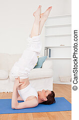 Young attractive red-haired female stretching in the living room in her apartment