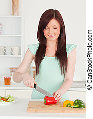 Gorgeous red-haired woman cutting some vegetables in the kitchen in her appartment