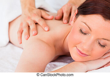 Closeup of a beautiful red-haired woman receiving a massage...