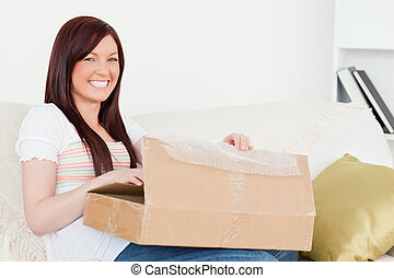 Beautiful red-haired woman opening a carboard box while sitting on a sofa in the living room