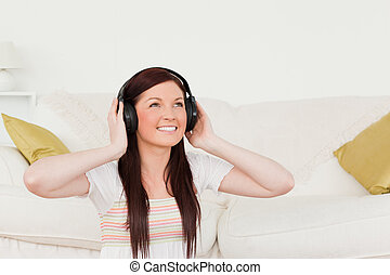 Pretty red-haired woman listening to music with headphones while sitting on a carpet in the living room