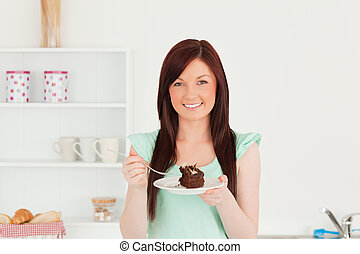 Good looking red-haired woman eating some cake in the...