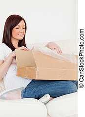 Good looking red-haired woman opening a cardboard box