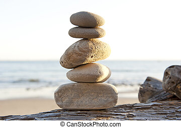 rock stack on driftwood with copy space - peace and...