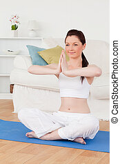 Young female doing yoga on a gym carpet