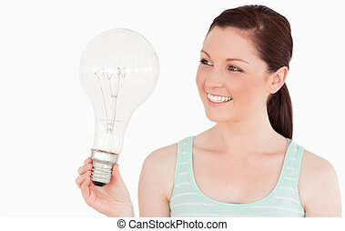 Attractive red-haired female holding a light bulb while standing on a white background