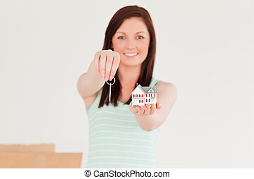 Attractive red-haired female holding a key and a miniature house standing on the floor at home