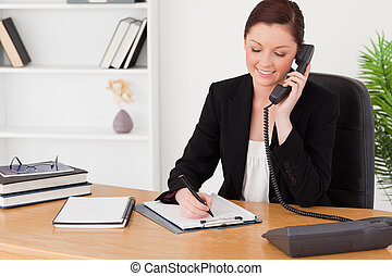 Beautiful red-haired woman in suit writing on a notepad and...
