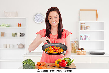 Pretty red-haired woman cooking vegetables in the kitchen in...