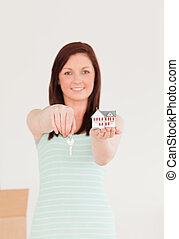 Good looking red-haired female holding a key and a miniature house standing on the floor at home