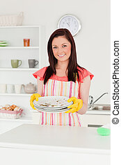 Gorgeous red-haired woman holding some dirty plates in the kitchen