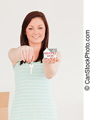 Beautiful red-haired female holding a key and a miniature house standing on the floor at home