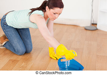 Cute red-haired woman cleaning the floor while kneeling at...